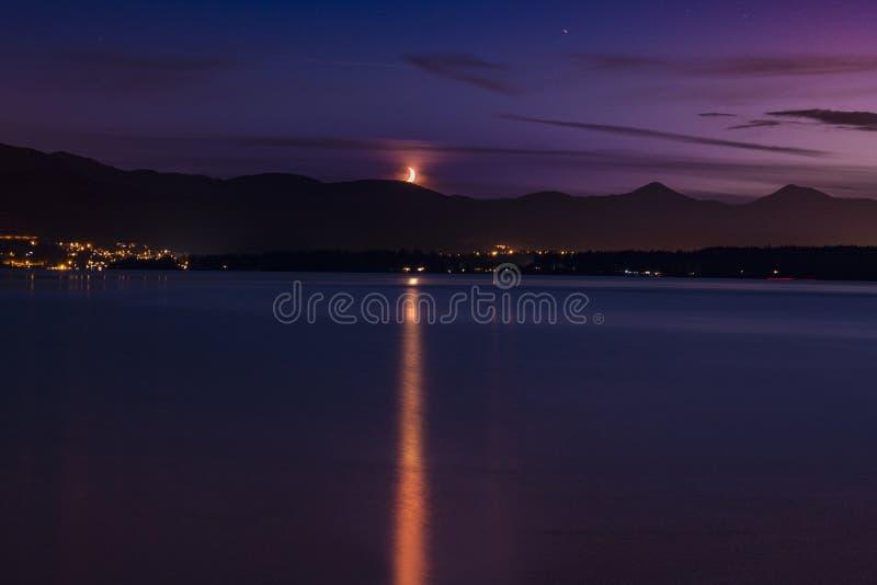Cielo púrpura del océano de la puesta del sol y de la luna foto de archivo libre de regalías