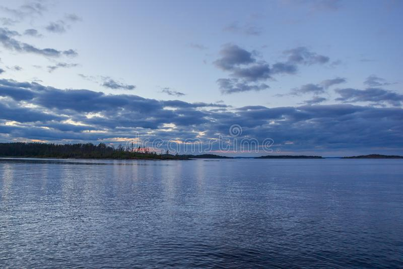 Cielo pesado de la puesta del sol de los azules marinos nublados profundos con paisaje por encima de la superficie de las luces r fotografía de archivo libre de regalías
