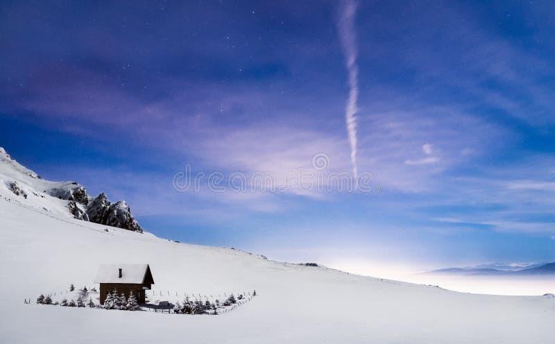 Cielo que sorprende del paisaje de la noche del invierno de la cabina de la montaña fotografía de archivo libre de regalías