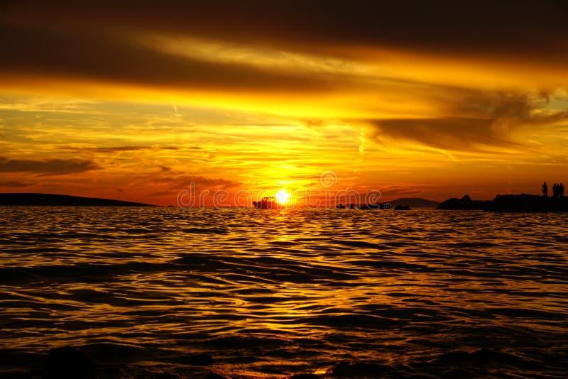 Cielo rosso e arancione drammatico al tramonto, sottofondo naturale con silhouette di barche e persone fotografia stock libera da diritti