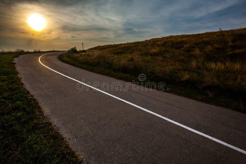 Cielo sopra la strada asfaltata vuota durante il tramonto Campo di dorato immagini stock libere da diritti
