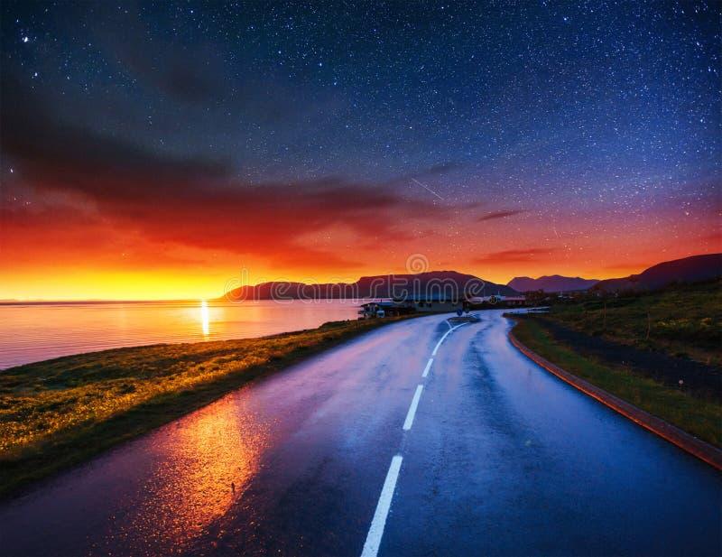 Cielo stellato sopra le montagne La strada asfaltata fotografia stock