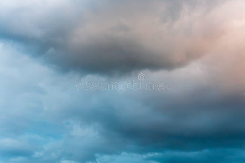 Cielo tempestuoso en el crepúsculo con las nubes en varios tonos de azul, de gris, y de anaranjado fotografía de archivo libre de regalías