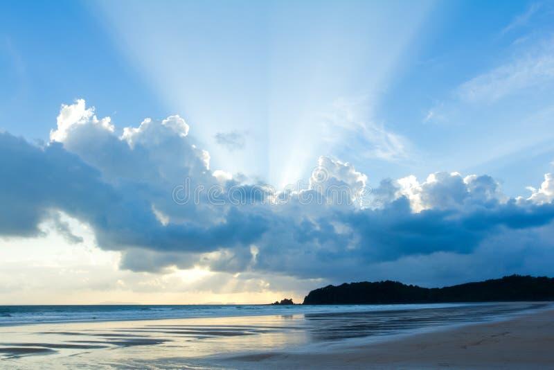 Cielo tropical de la puesta del sol de la playa con las nubes encendidas foto de archivo libre de regalías