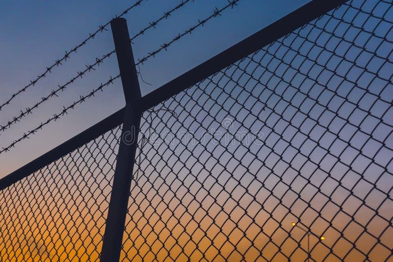 Cielo uguagliante crepuscolare di crepuscolo con i recinti ed il filo spinato fotografia stock