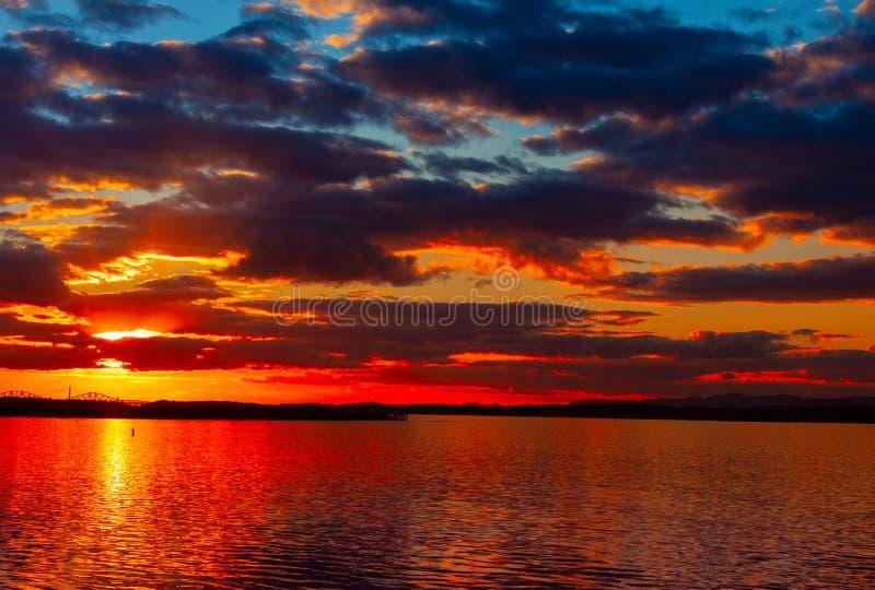 Cielo vibrante colorido dramático de la puesta del sol con las nubes reflejadas en el agua fotos de archivo