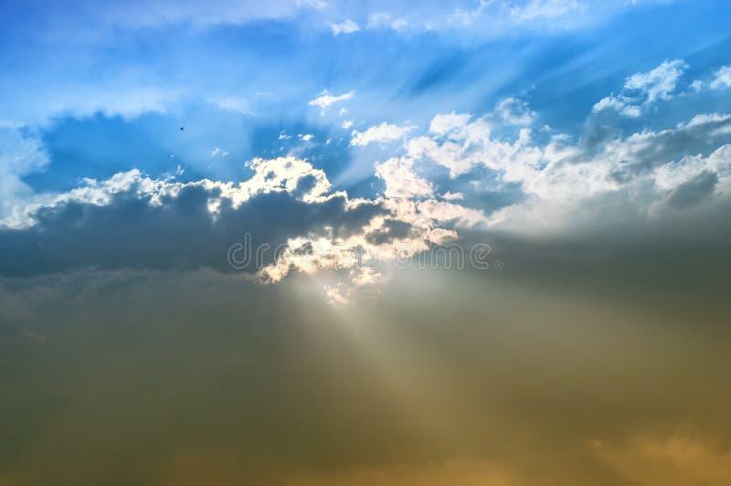Cielo vibrante con el sol detrás de las nubes y de los rayos del sol foto de archivo