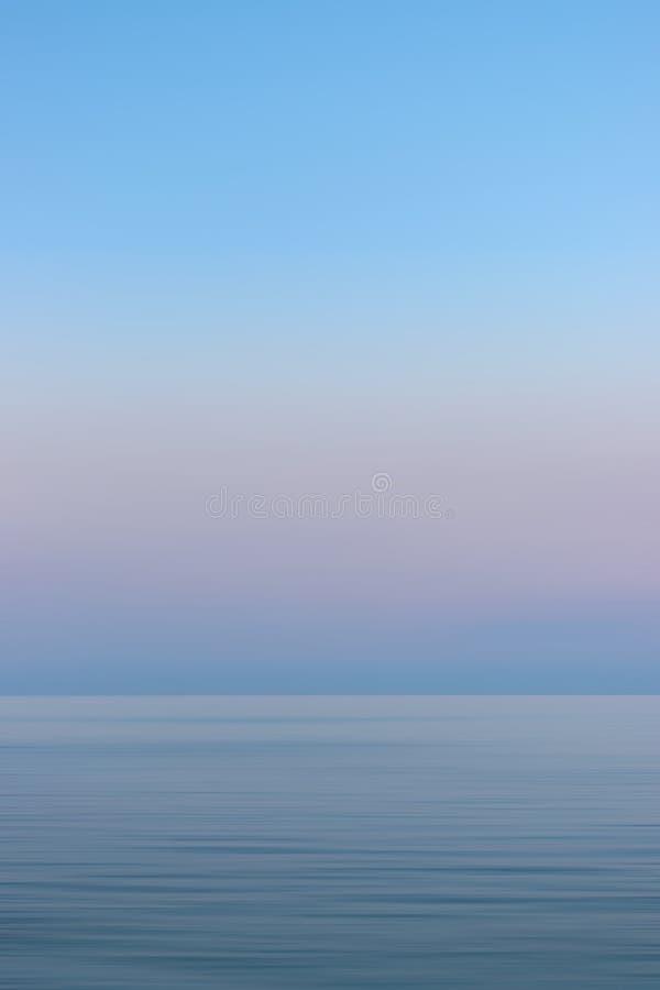 Cielo y mar coloridos de la puesta del sol con el movimiento borroso imagen de archivo libre de regalías