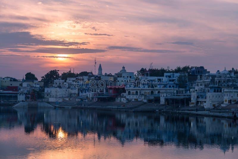 Cielo y nubes coloridos sobre Pushkar, Rajasthán, la India Templos, edificios y colores reflejando en el agua santa del lago en fotografía de archivo libre de regalías