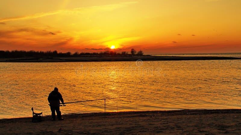 Cielo y pescador anaranjados de la puesta del sol fotografía de archivo libre de regalías