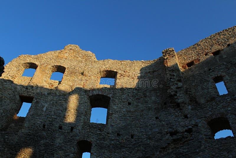 Cielos azules y diversas ventanas en restos de la pared del este del patio interno gótico temprano del castillo Topolcany, Eslova foto de archivo