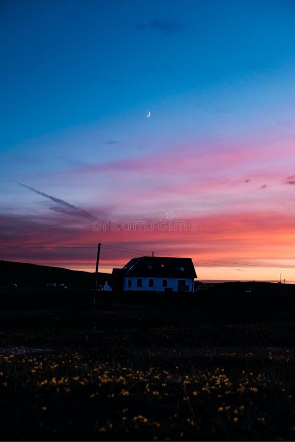 Cielos imponentes y luna creciente sobre una casa sola fotos de archivo