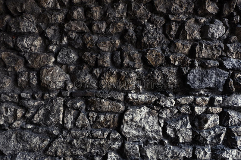 Ciemna kamienna ściana robić nieregularne i szorstkie skały zdjęcia stock