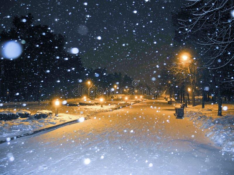 ciemna mroźna noc parka zima Opad śniegu i pomarańczowego światła lampiony zdjęcia stock