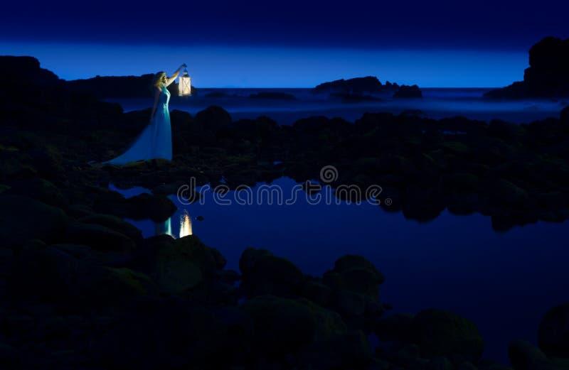 Ciemna noc, błękitny morze i niebo, blondynki kobieta w długiej sukni z lampionem fotografia stock