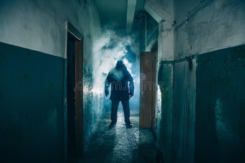 Ciemna sylwetka dziwaczny niebezpieczeństwo mężczyzna w kapiszonie w plecy świetle z dymem lub mgle w strasznym grunge korytarzu, obraz stock