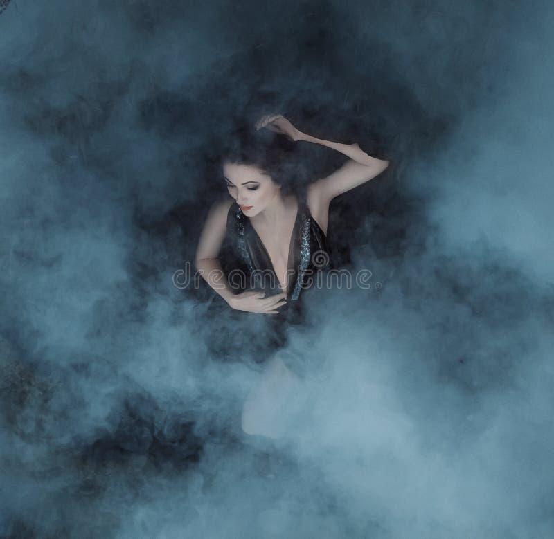 Ciemna wampir królowa kłama w uścisku mgły na jej czarnej sukni z głębokim neckline Dziewczyna odkrywa wewnątrz fotografia stock