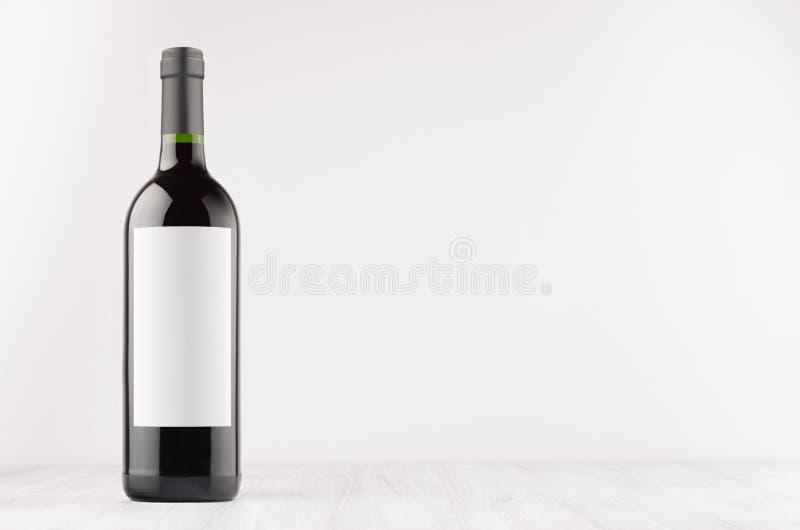 Ciemna wino butelka z pustą białą etykietką na białej drewnianej desce, wyśmiewa up fotografia royalty free