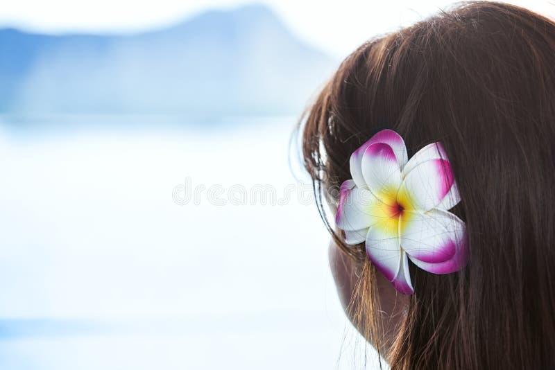 Ciemna z włosami dziewczyna jest ubranym Hawajskiego kwiatu patrzeje widok na ocean zdjęcia royalty free