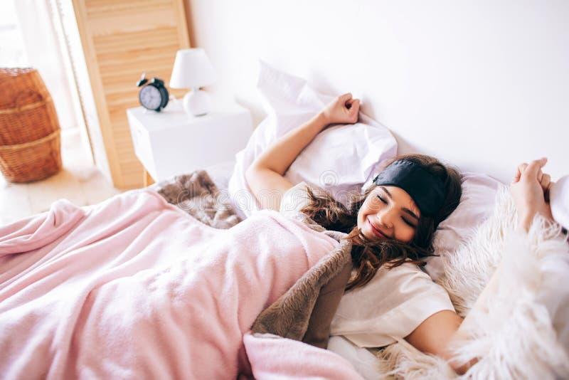 Ciemna z włosami piękna młoda brunetka budzi się w jej łóżku Rozciągać ręki i bosdy K?ama? na ? zdjęcia stock