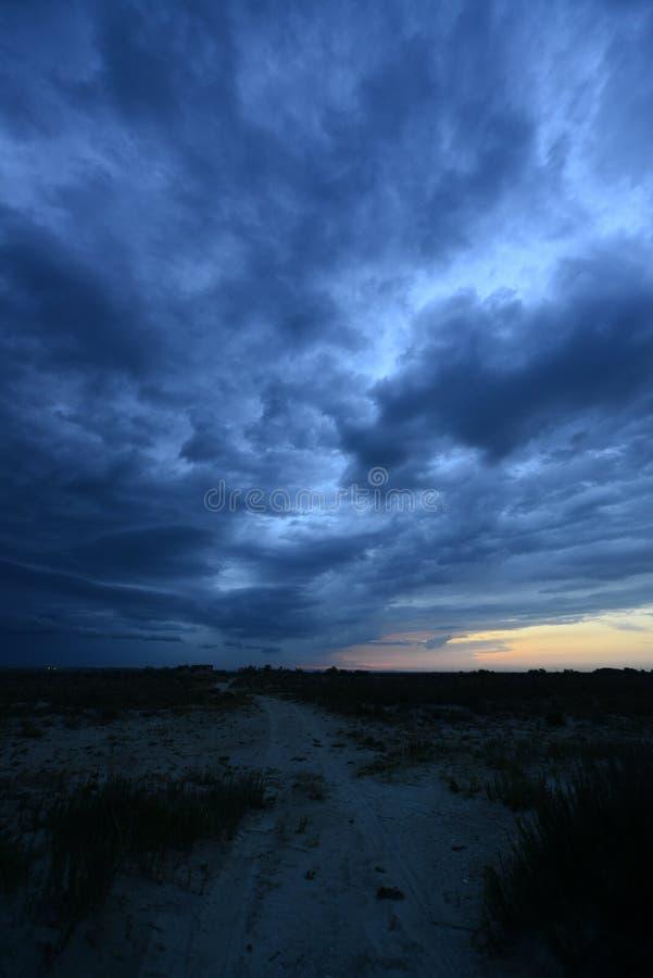 Ciemne burz chmury nad piasek droga w stepie obrazy stock