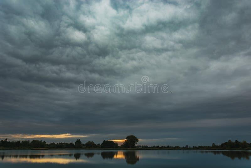Ciemne dżdżyste chmury stacza się nad jeziorem fotografia stock