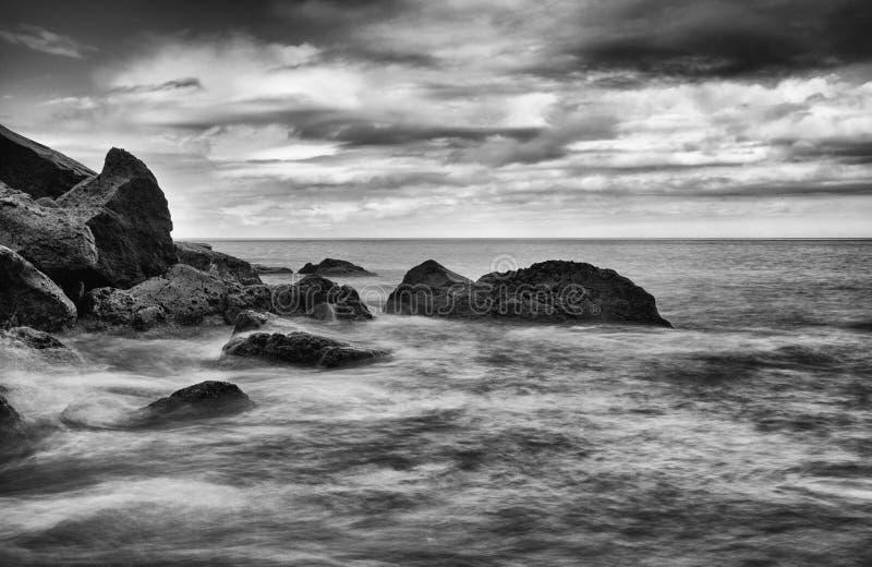 Ciemne niebo ze skałą i oceanem obraz stock