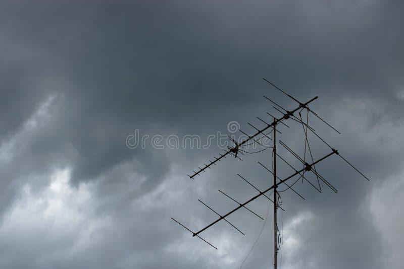 Ciemne potężne burz chmury przed deszczem przeciw starej telewizyjnej antenie na dachu obraz stock