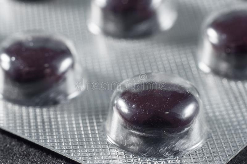 Ciemnego brązu pigułki w specjalnych medycznych kijach, w górę zdjęcie stock
