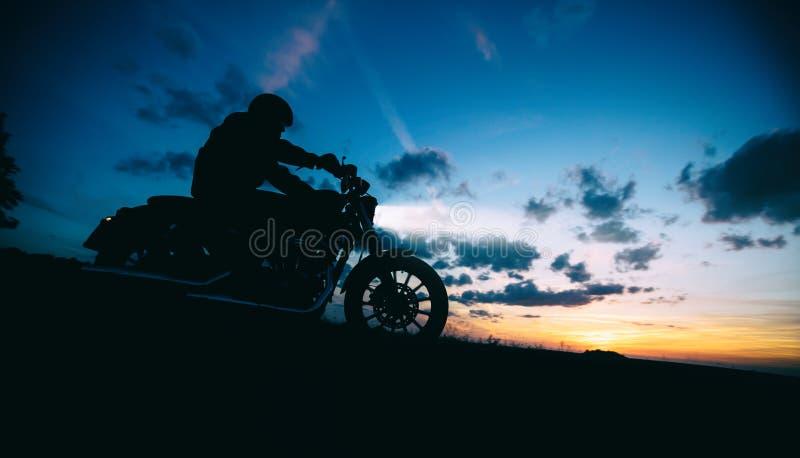 Ciemnej motorbiker sylwetki dużej mocy jeździecki motocykl zdjęcie royalty free