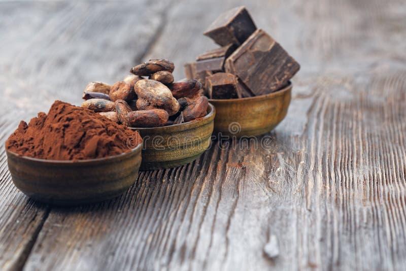 Ciemni czekoladowi kawałki, kakaowy proszek i kakaowe fasole, zdjęcia royalty free