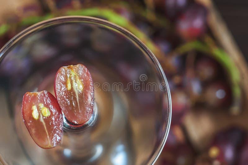 Ciemni winogrona cią w połówce z kościami inside w lekkim przejrzystym wina szkle na zmroku stołu zakończeniu w centrum zdjęcia stock