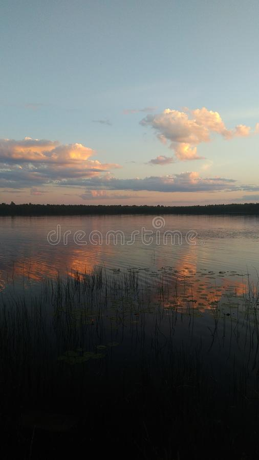 Ciemnopąsowy zmierzch nad lustrzanym jeziorem zdjęcie stock