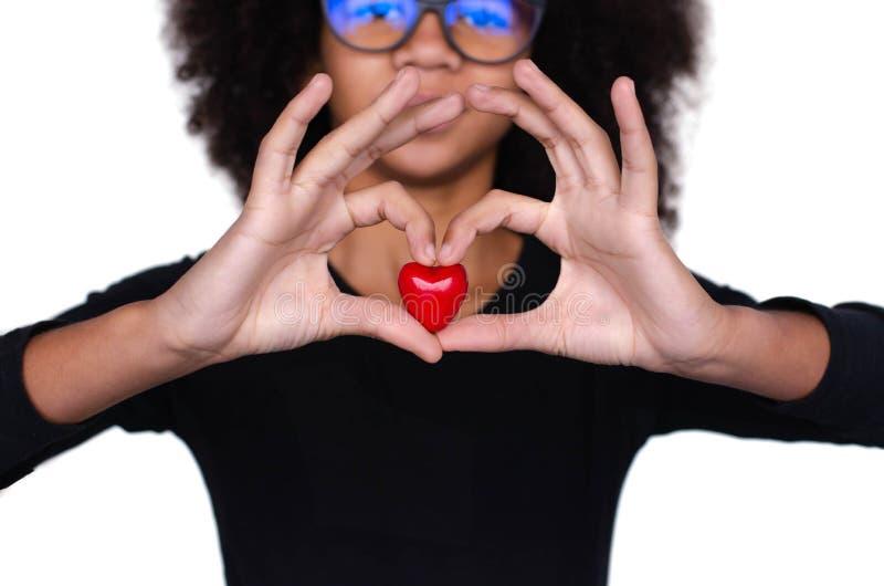 Ciemnoskóra kędzierzawa dziewczyna trzyma czerwonego serce zdjęcie royalty free