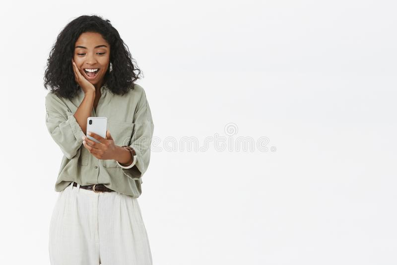 Ciemnoskóra kobieta otrzymywa ślicznego pic przez interneta ono wpatruje się przy smartphone ekranu dotykającą i zadowoloną macan fotografia royalty free