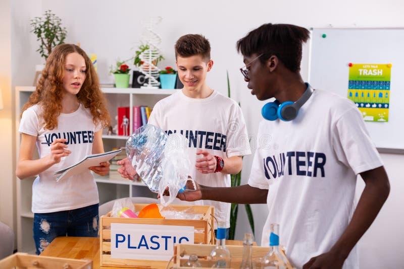 Ciemnoskóry nastolatek daje butelce przyjaciel podczas gdy sortujący odpady zdjęcia royalty free