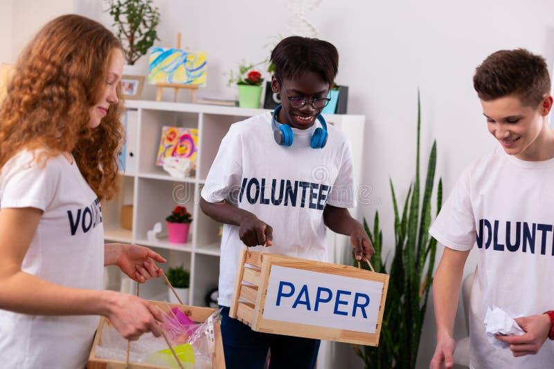 Ciemnoskóry nastolatek trzyma pudełkowaty z papierem w szkłach fotografia stock