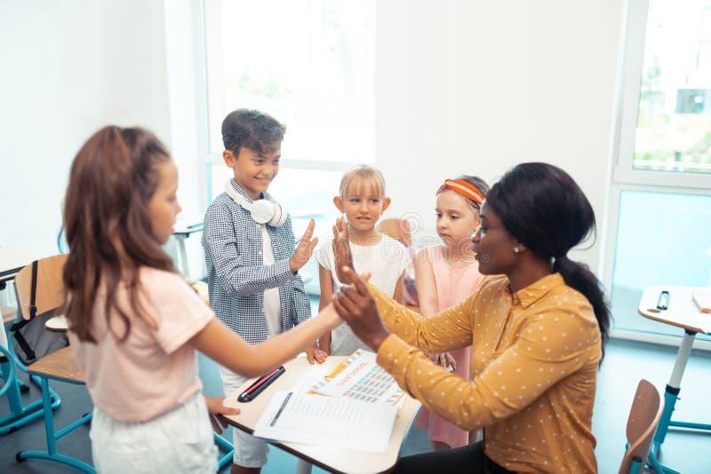 Ciemnoskóry nauczyciel daje wysokości pięć jej mądrze śliczni ucznie zdjęcia stock