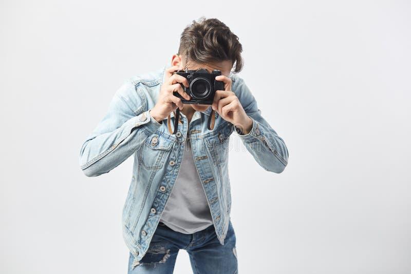 Ciemnowłosy facet ubierający w białej koszulce, cajgach i drelichowej kurtce, robi fotografiom na kamerze na białym tle wewnątrz obraz stock