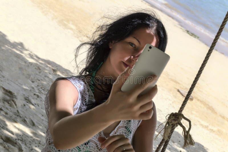 Ciemnowłosa kobieta ono fotografuje w tropikalnej plaży zdjęcie stock