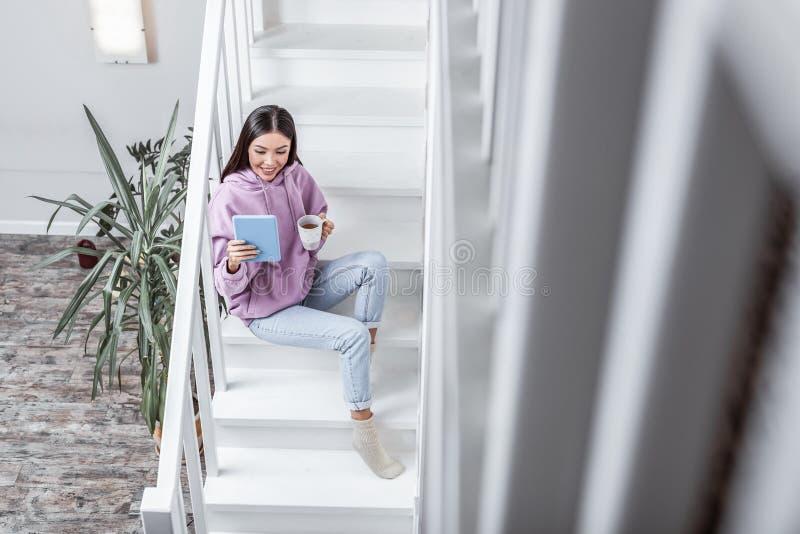 Ciemnowłosa kobieta pije herbaty i czytanie elektronicznej książki fotografia stock