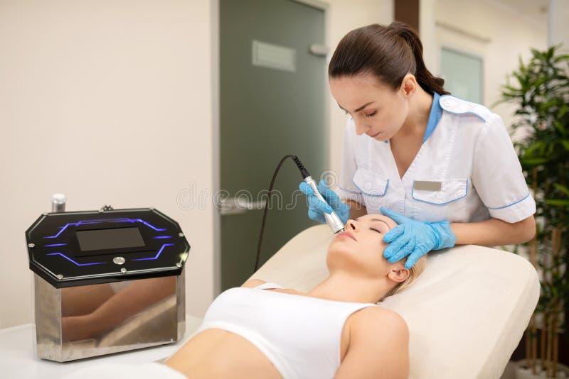 Ciemnow?osy dermatolog robi laserowemu sk?ry traktowaniu dla kobiety obrazy royalty free