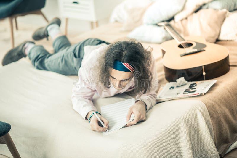 Ciemnowłosy skupiający się artysty lying on the beach w łóżku i działaniu na tworzeniu fotografia royalty free