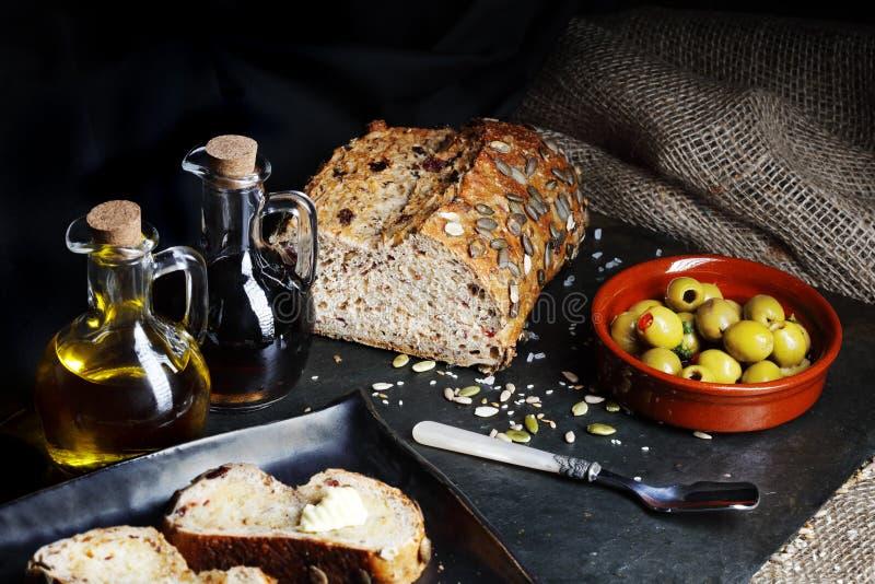 Ciemny jedzenie - Świeży dyniowego ziarna chleb z oliwkami zdjęcia stock