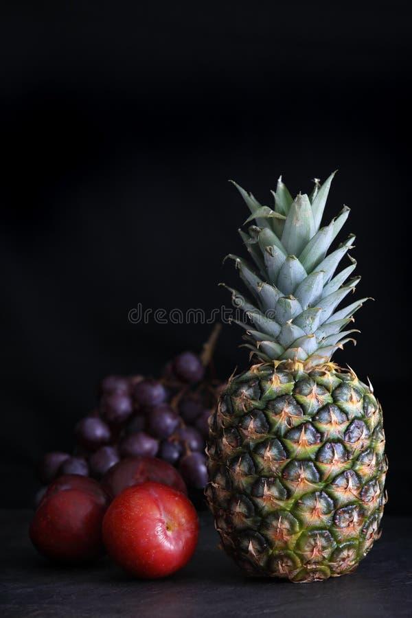 Ciemny jedzenie - ananas z ciemnego czerni czerwonymi winogronami i czerwonymi śliwkami zdjęcia royalty free