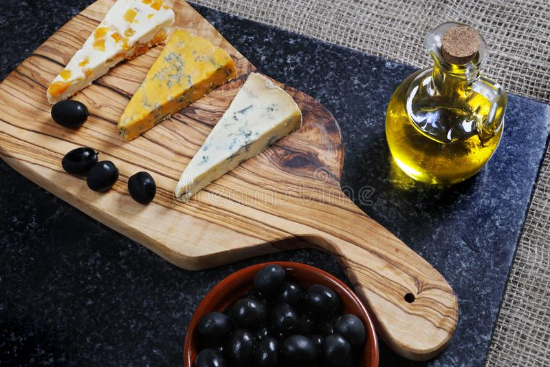 Ciemny jedzenie - Błękitni sery na oliwnym drewnie wsiadają zdjęcie stock