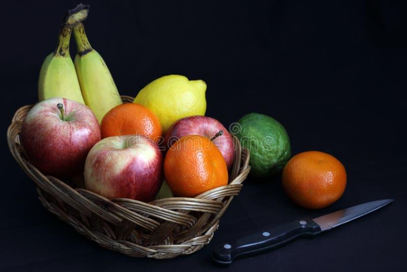Ciemny jedzenie - Chiaroscuro mieszał owoc w łozinowym koszu obrazy stock