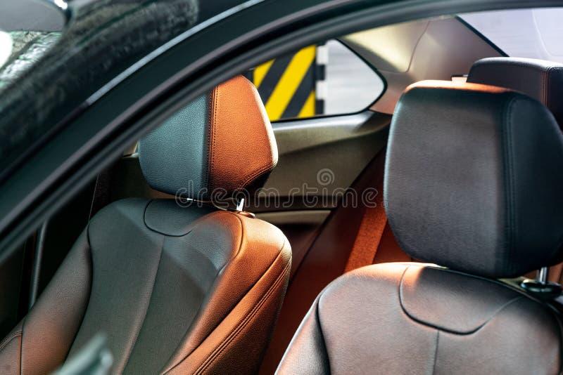 Ciemny luksusowy nowy samochodowy wnętrze Tylni miejsce pasażera w nowożytnym samochodzie, boczny widok fotografia stock