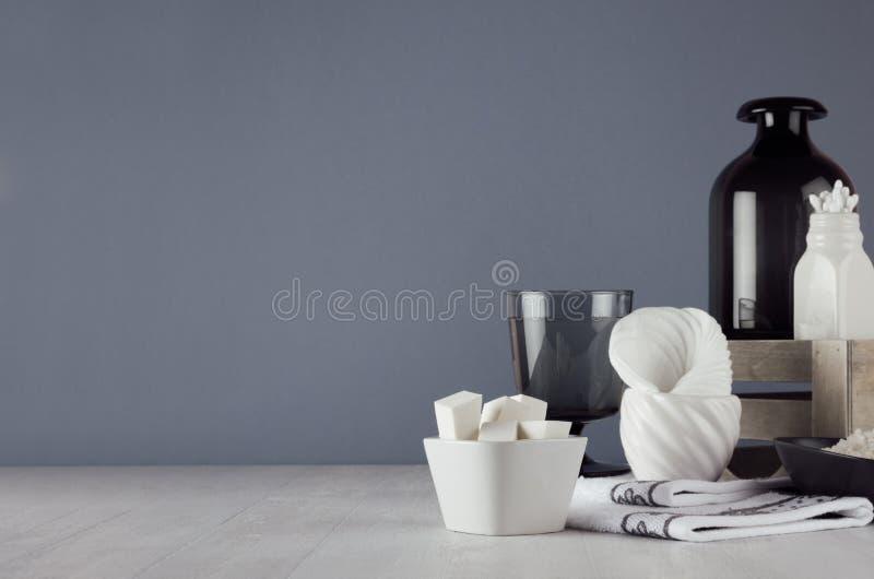 Ciemny minimalistic łazienka wystrój - ciemnego szkła waza, drewna pudełko, ręcznik, produkty i akcesoria dla opieki, stawiamy cz zdjęcia stock