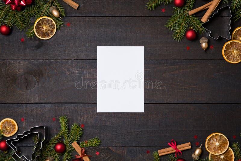 Ciemny nieociosany drewno stół flatlay - nutowa karta na Bożenarodzeniowym tle z dekoracji i jodły gałąź ramą Odgórny widok z bez obraz royalty free